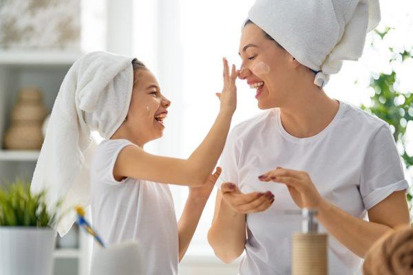 Mère et sa fille se passant de la crème hydratante sur le visage